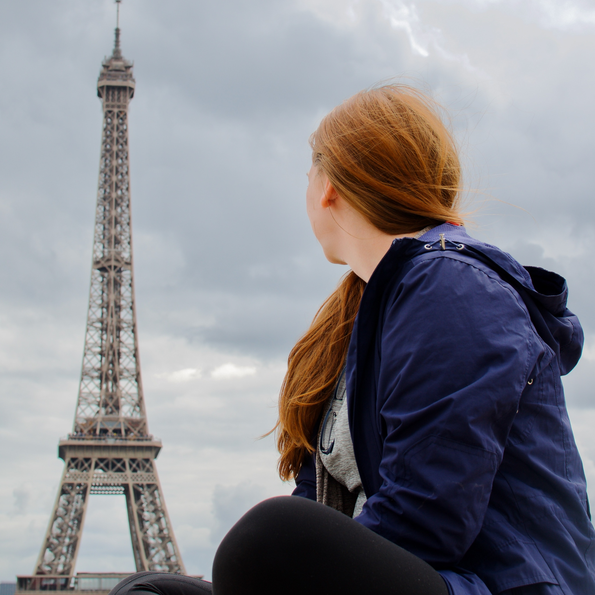Woman in purple coat with red hair, looking towards the Eiffel Tower on a cloudy day