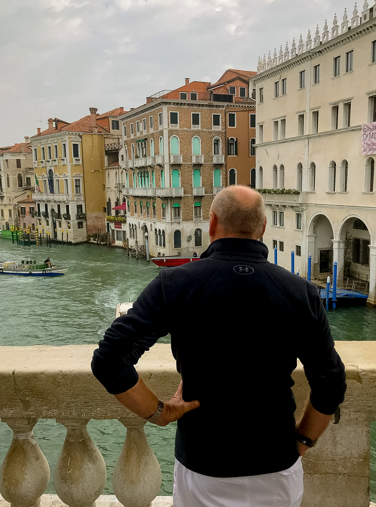 Man in black with left hand on hip, overlooking Venice's Grand Canal on his first trip to Italy. The green murky canal is lined with old multi-colored buildings.