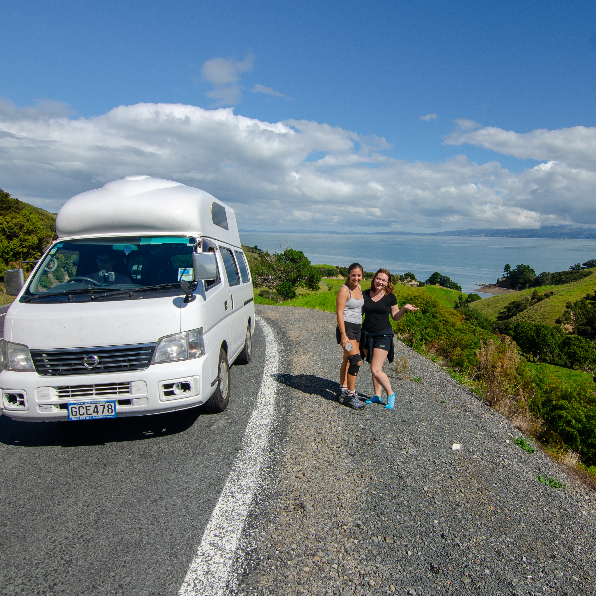 Two women stand alongside a white campervan parked on the road, with lush green rolling hills and icy blue water in the background