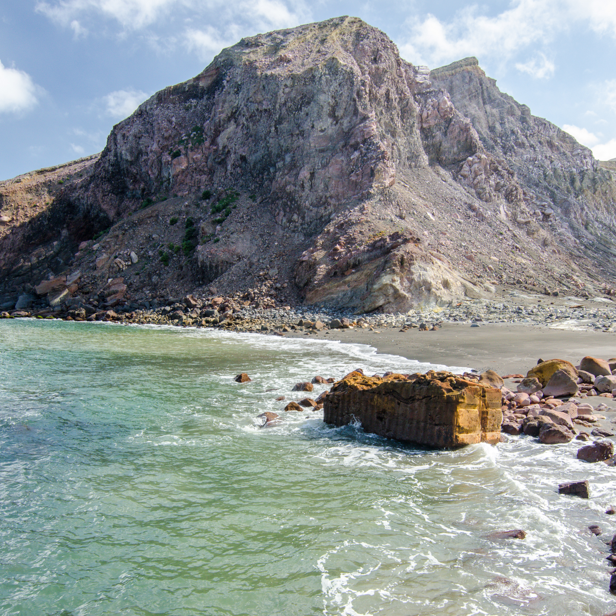 Barren volcanic mountain on White Island, with a foreground of green water and rusted remnants of life on the island.
