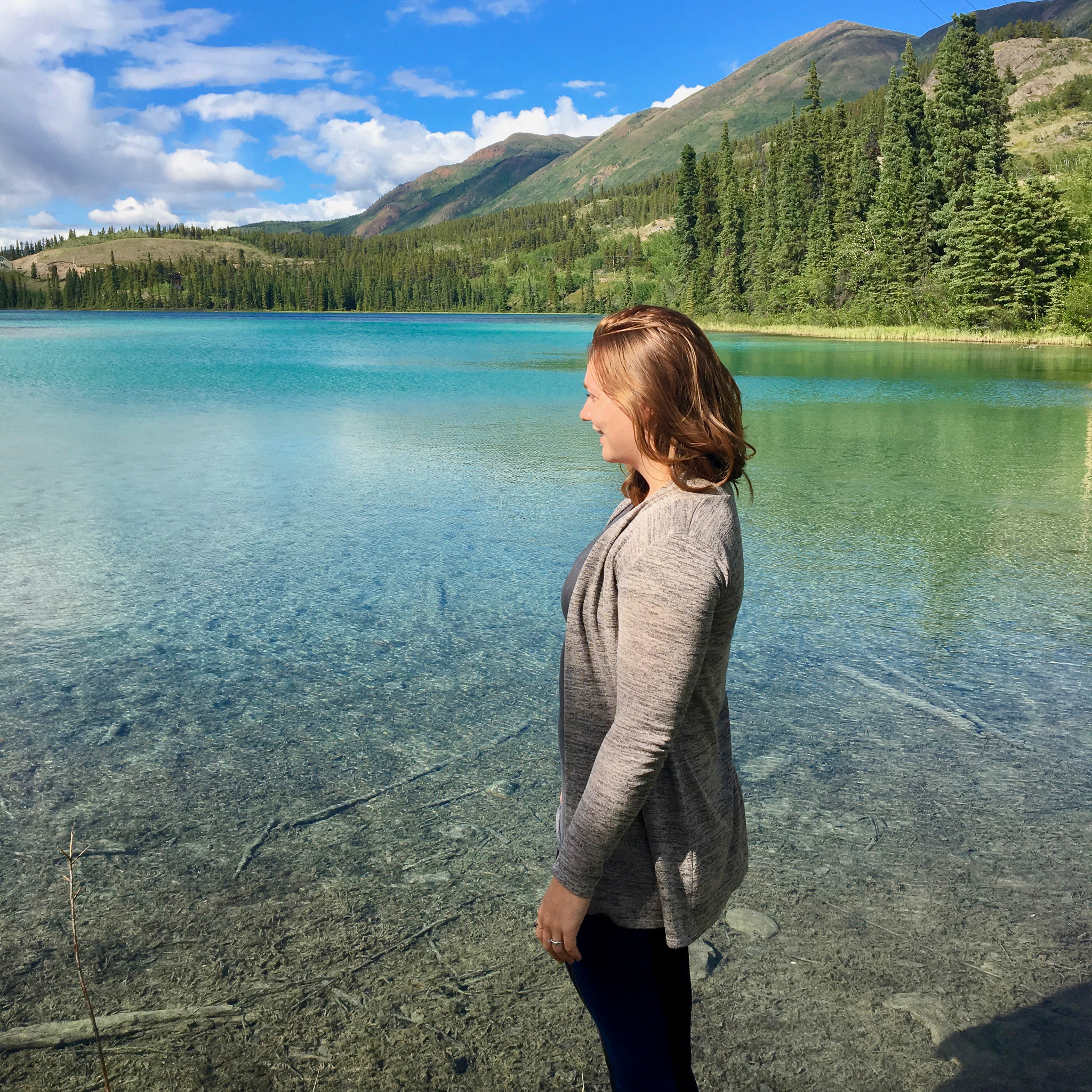 Woman looking out at emerald colored lake, surrounded by mountains and blue sky