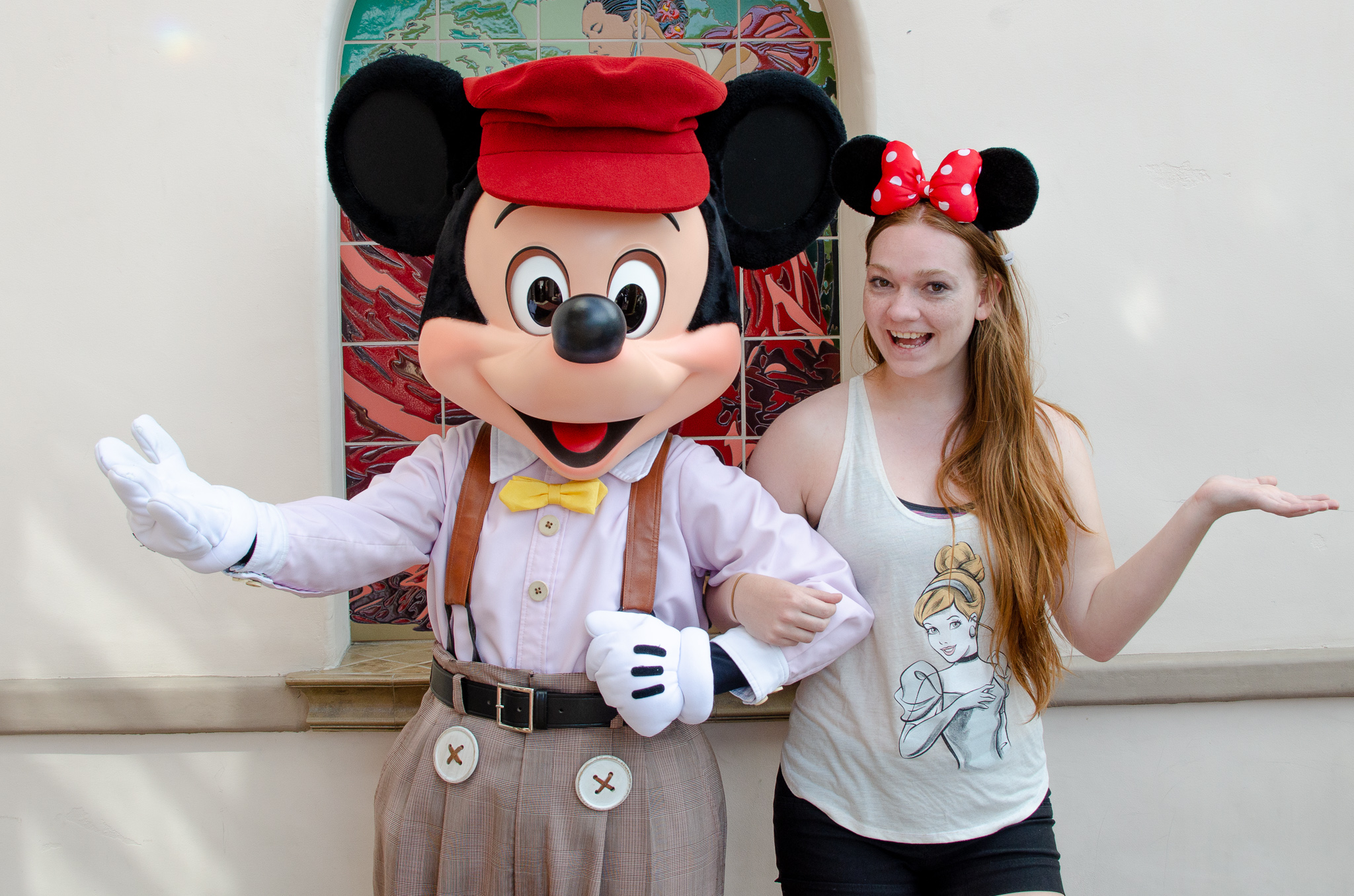 Mickey dressed up in red hat, white shirt and beige suspenders, standing beside woman in red Miinnie ears