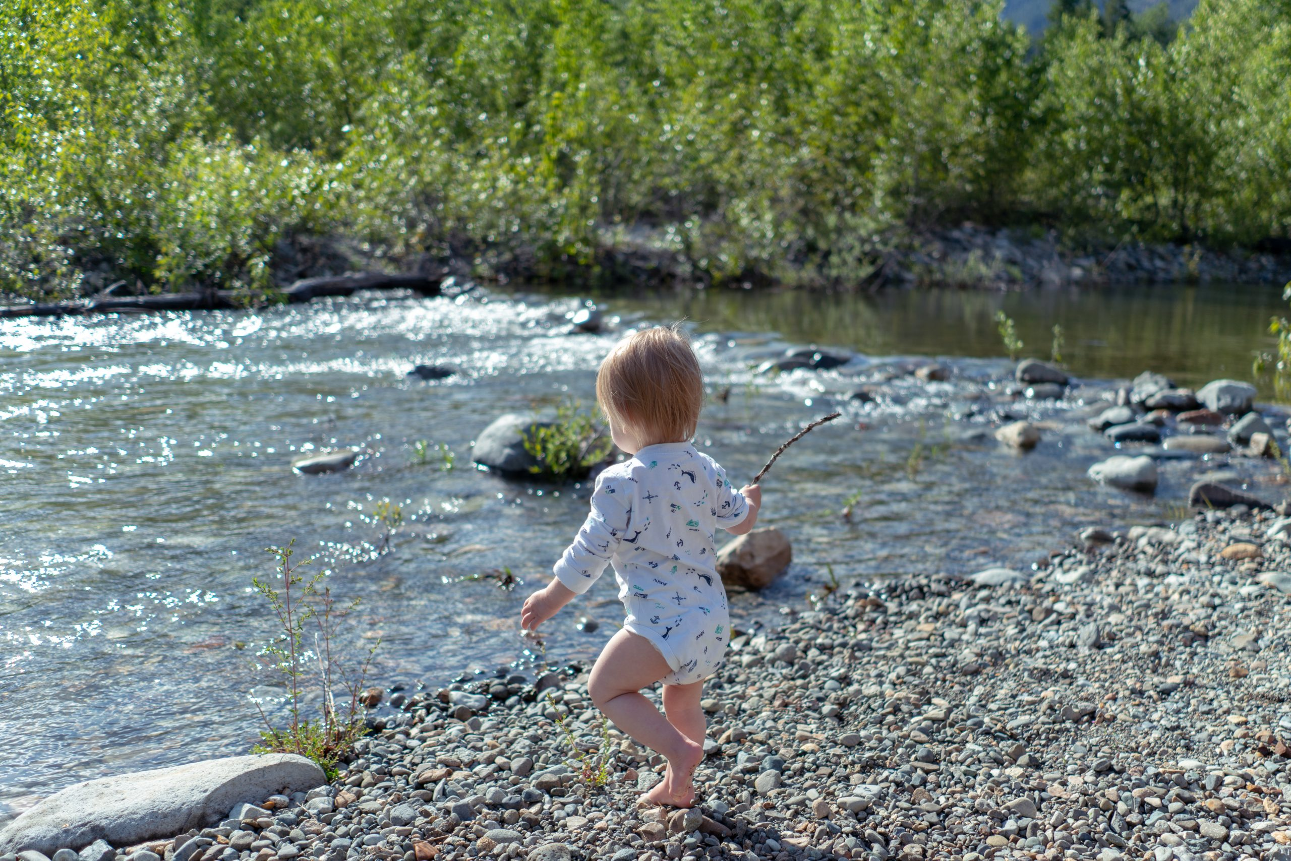 Toddler playing with a stick at the edge of a river